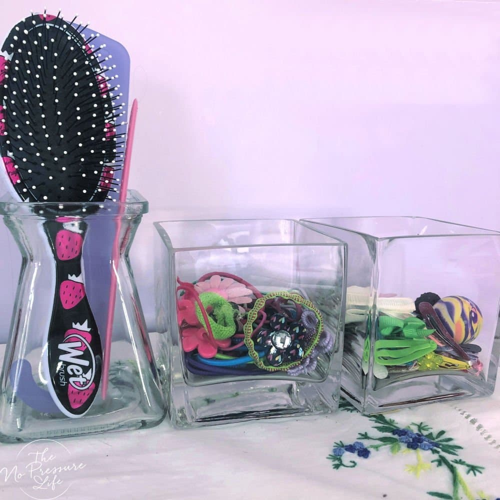 DIY hair accessory organization with brushes, elastics, and clips in glass vases