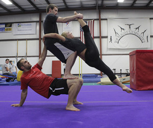 Photo by Maggie Pund NKU student Kirk Wallace practices Acro-yoga with fellow gymnasts at Top Flight Gymnastics. Every week at the gym, Wallace can be seen teaching or practicing with friends Andrew Goeeicke and Kayla Ferguson.