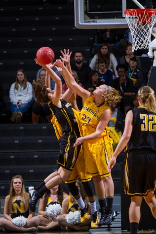 NKU women's basketball player Christine Roush (left) goes up for the layup against Kasey Uetrecht (23) during the scrimmage at Black and Gold Madness. NKU's 2014 Black and Gold Madness was held at the Bank of Kentucky Center on October 9, 2014 celebrating the start of the 2014-15 season.