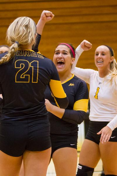 NKU's Lauren Hurley (center) celebrates after a scored point with Jayden Julian (left) and Mel Stewart (right). Lauren had 4 aces during NKU's 3-0 win against Jacksonville at Regents Hall on October 11, 2014.