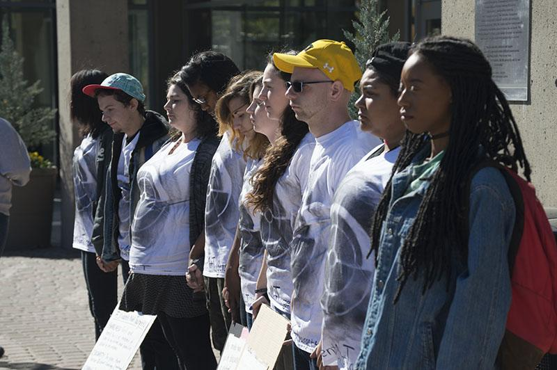 Students stand during the silent protest bringing awareness to school shootings and gun violence. The protest was organized by Students for Social Change.