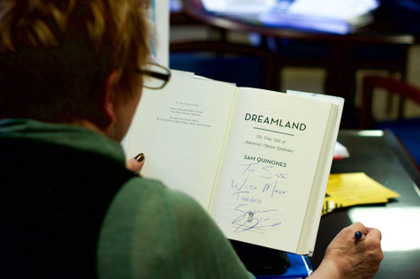 "Provost Sue Ott Rowlands reviews her signed copy of ""Dreamland."" She has been coordinating Quinones' visit to campus since last summer."