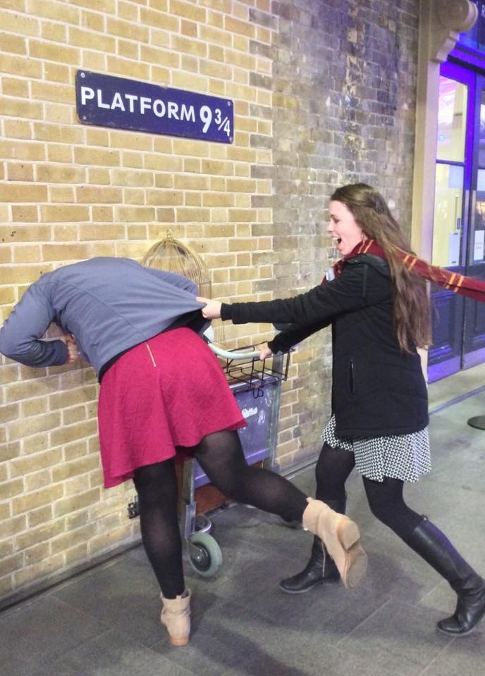 Two students pose at the platform 9 3/4 entrance at the train station in London.