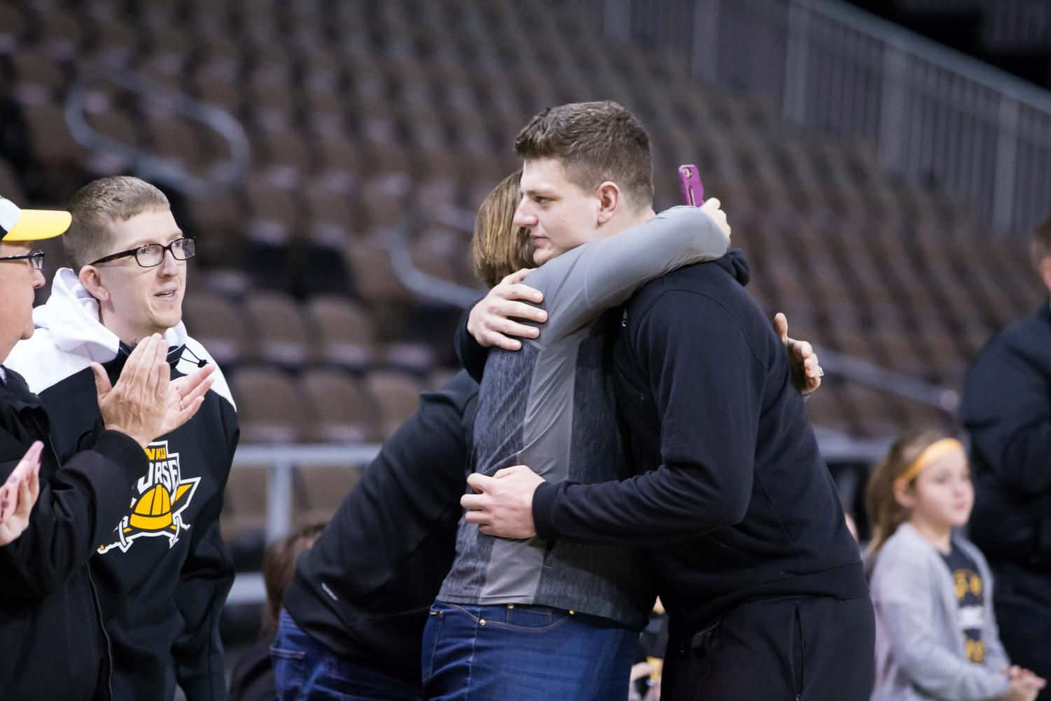 Drew McDonald (34) hugs his mother before the net cutting in BB&T Arena after securing 1st place in Horizon League.
