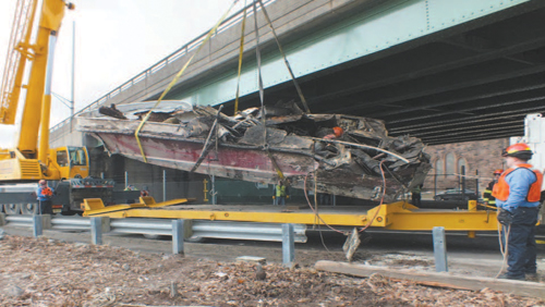 Photo courtesy Chris Brooks From top.: PVSC excavator re-positions boat, then crane begins to lift vessel, and deposits mangled remains into flatbed trailer under highway.