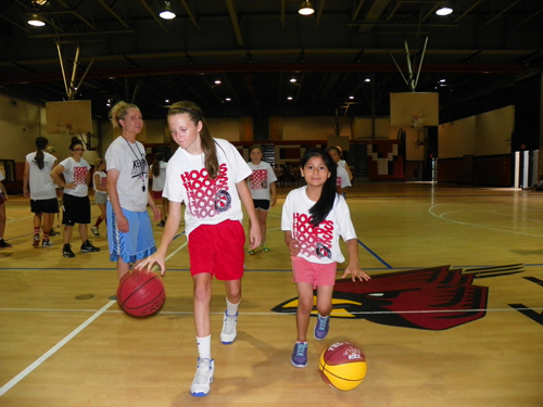Photo by Jim Hague As Kearny High School head coach Jody Hill (far l.) looks on, Meagan McClelland (l.) and Emily Angeles display some of their ball handling skills at the annual Kearny High School Girls' Basketball Camp recently