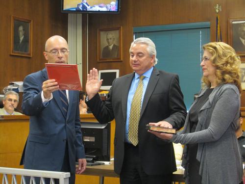 Photo by Ron Leir With his wife, Maria, holding the Bible, John Peneda (c.) is sworn in as new assessor by Mayor Alberto Santos at June 25 council session.
