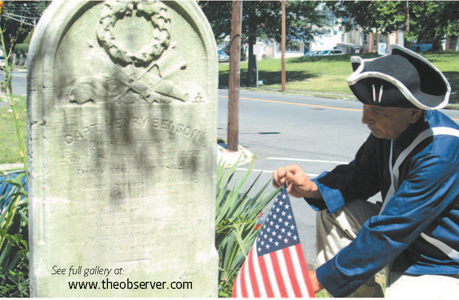 Photo by Ron Leir Michael Perrone adjusts flag at grave of Civil War Capt. Henry Benson.
