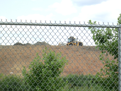 Photos by Ron Leir Earth-mover flattens out top of mound at landfill.