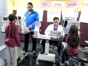 Photo by Ron Leir Optical Academy staffers check eyesight of East Newark students.