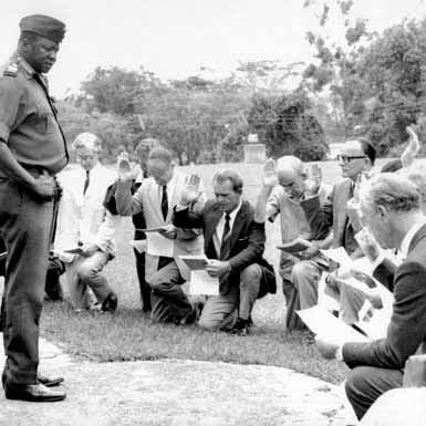 White diplomats bowing down to president Amin whilst reciting 'Oath of Allegiance' to him as a ruler of Uganda