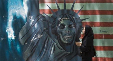Iranian woman walks by street art