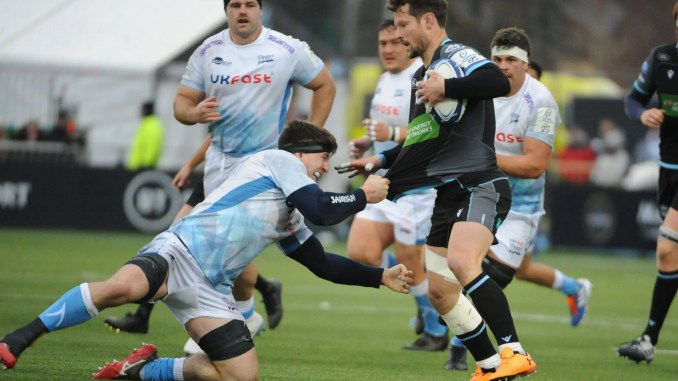 Warriors substitute Pete Horne tries to hand off Sharks flanker Ben Curry.