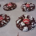 Chocolate crinkle cookies with red and white striped kisses on parchment paper