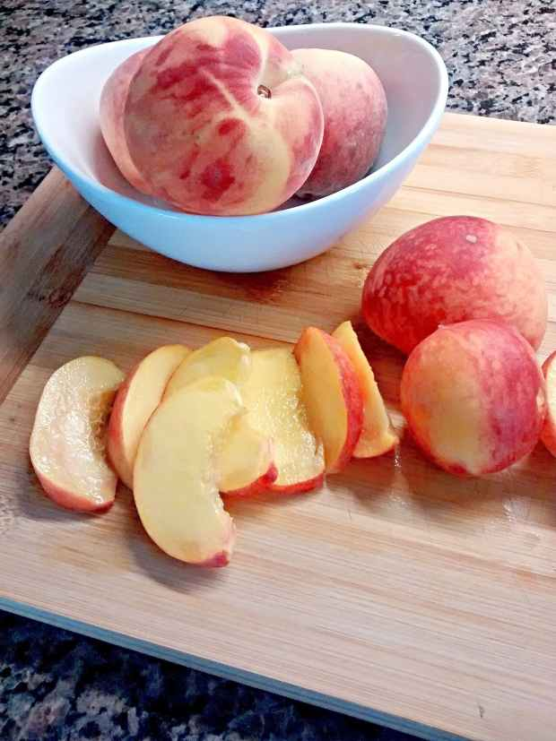 Fresh peaches sliced on cutting board with white ceramic bowl full of whole peaches