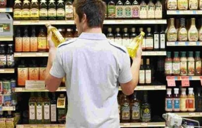 Shopper in supermarket choosing olive oil