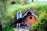 An average human male (Dan McBride) stands in front of a small Hobbit door.