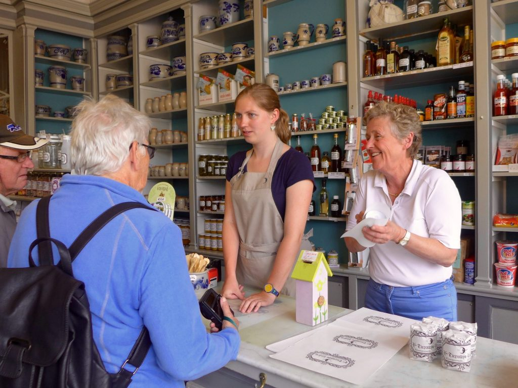Shop owners assisting customers in a mustard shop in Ghent, Belgium.Visiting Europe is a bucket list goal for many.