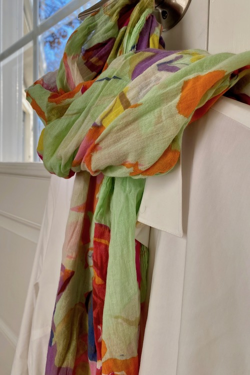 womans white shirt with colorful scarf, a key way to pack light