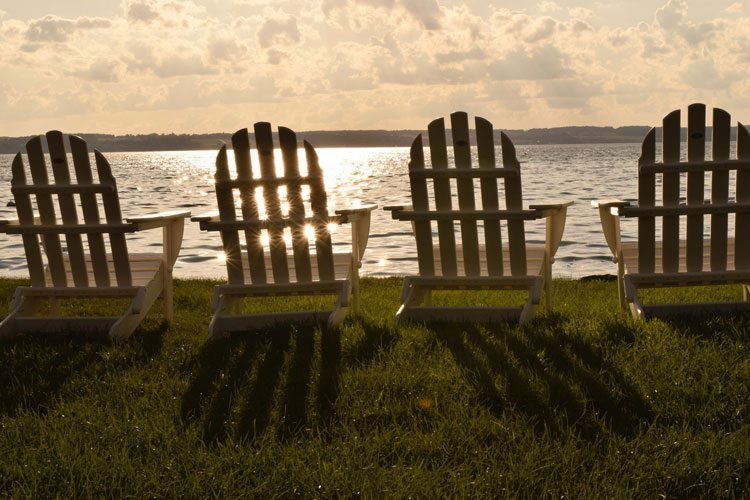 4 Adirondack chairs at sunset in Aurora, NY, a great trip idea for a new year