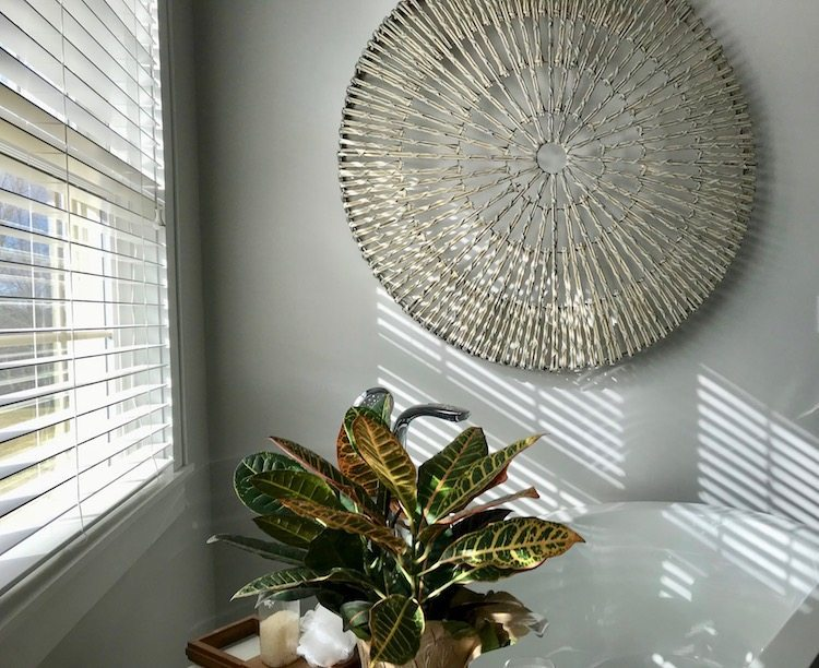 Woven willow wheel from Pottery Barn makes the perfect spa bathroom statement and is a great way to feature big wall art.