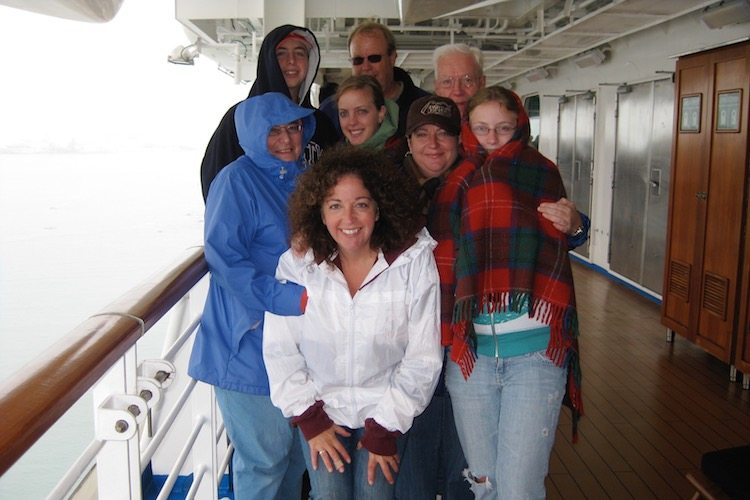 family gathered on Alaskan cruise deck showing a good cruise packing tip is to know the weather