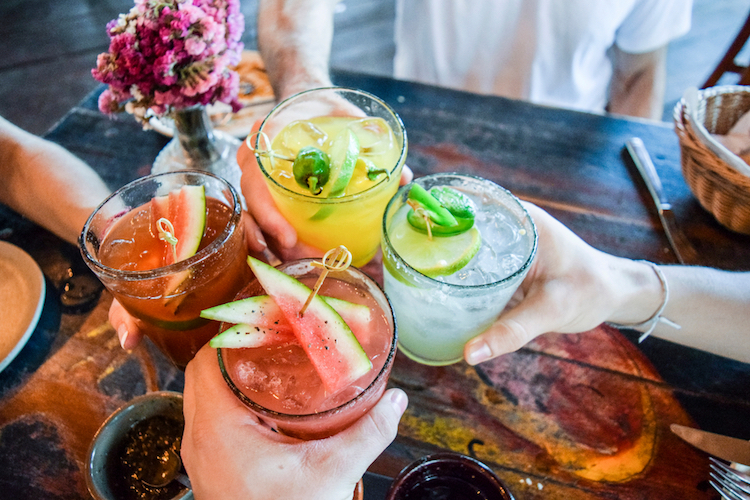 friends toasting happy hour with pretty cocktails