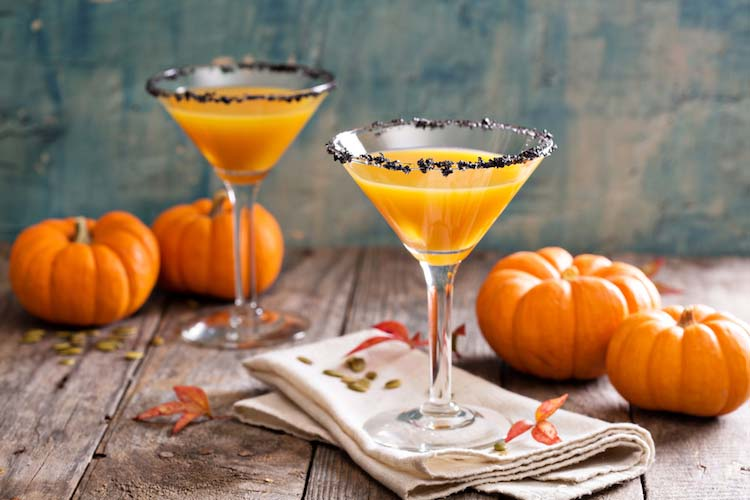 two Halloween cocktails with small pumpkins on a farm table