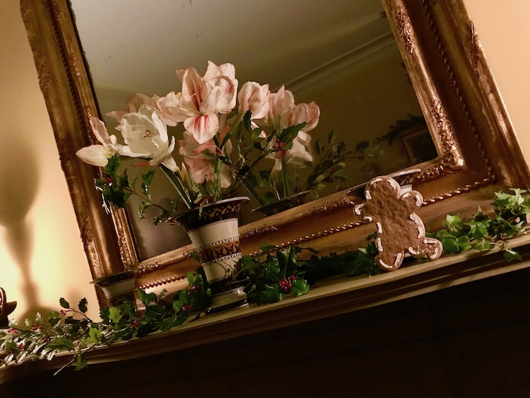 greens, flowers and a gingerbread man on a mantel at Boscobel during holiday twilight tours