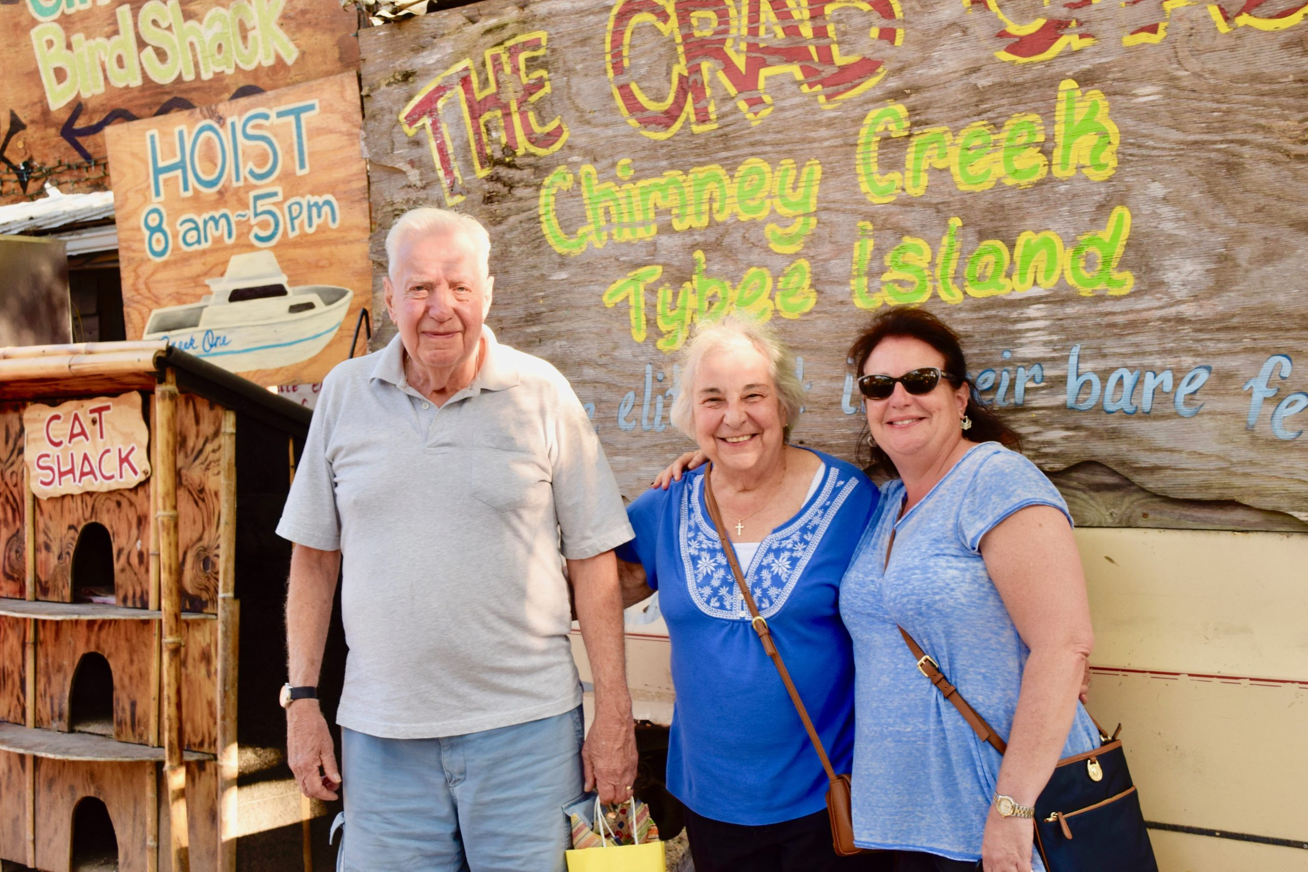 parents and daughter in front of Tybee Island crab shack sign