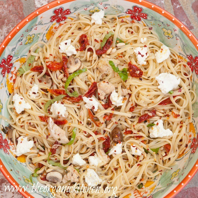 A brightly colored bowl filled Linguini with Chicken and Goat Cheese and garnished with basil