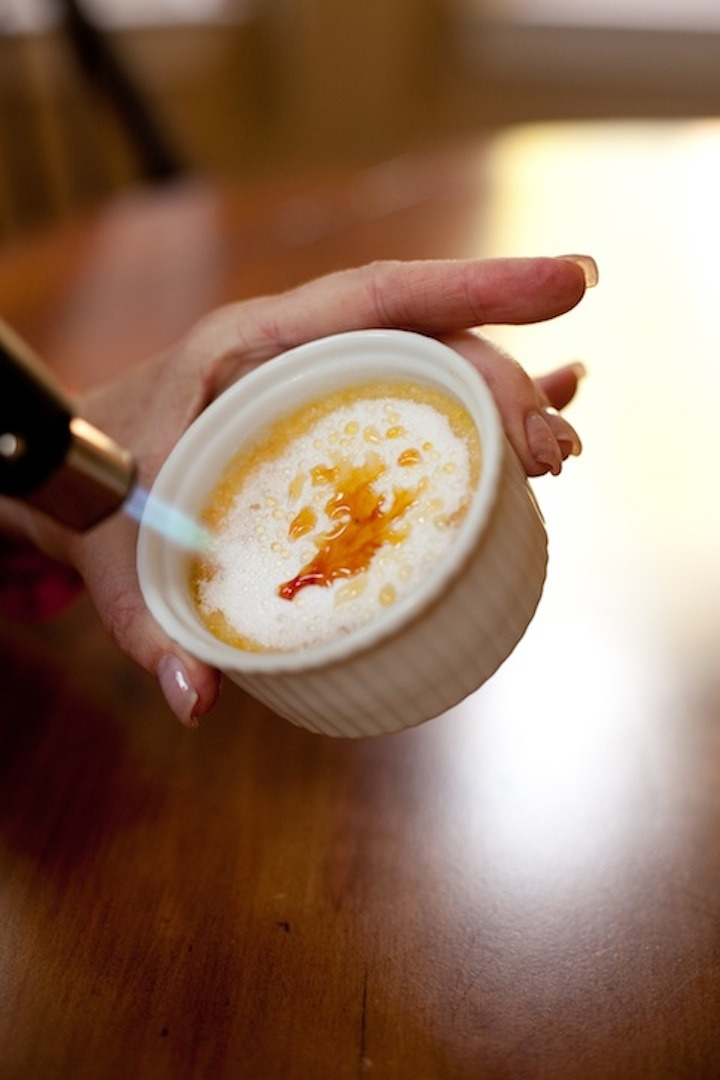 A female's hand torching sugar on Orange Vanilla Creme Brûlée
