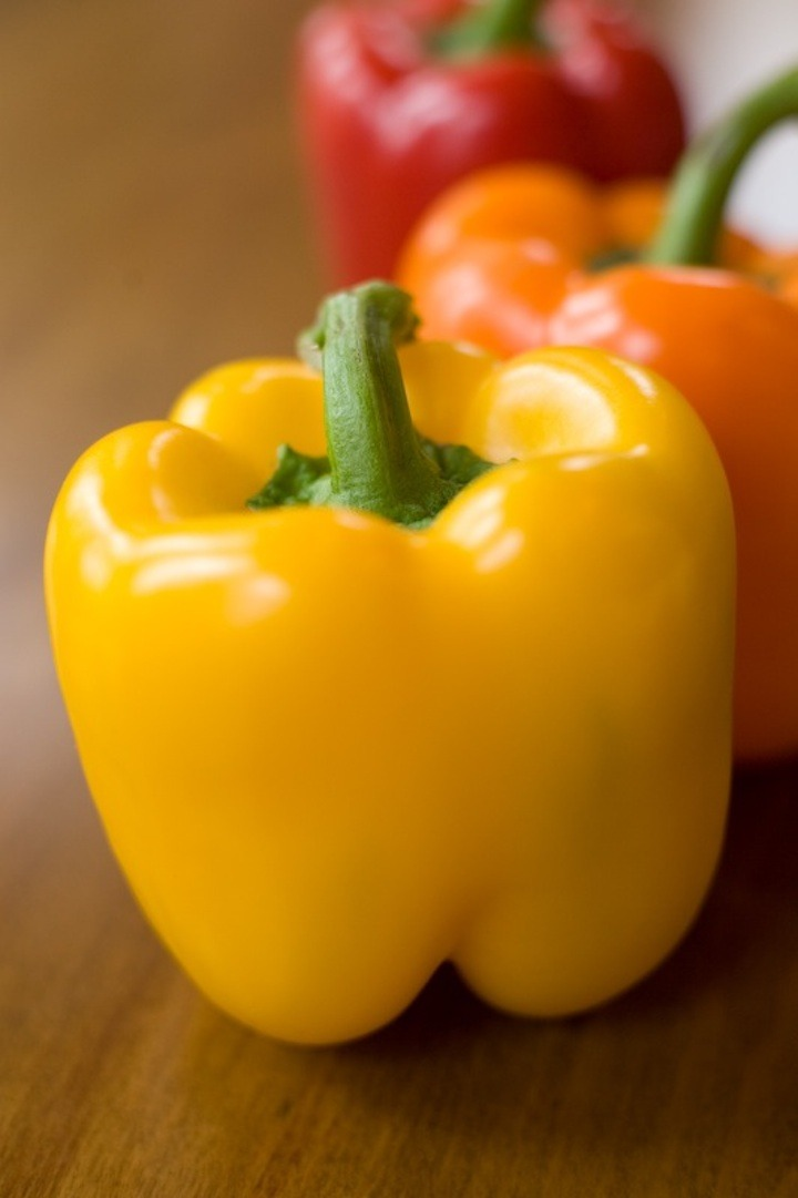 A yellow, orange and red bell pepper on a wood surface