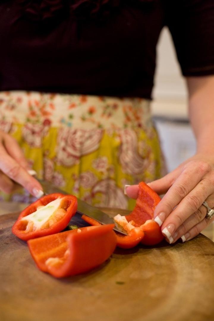 A females hands cutting a red bell pepper on a cutting board