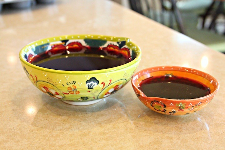 Two bowls of pomegranate juice, one before reduction, one after.
