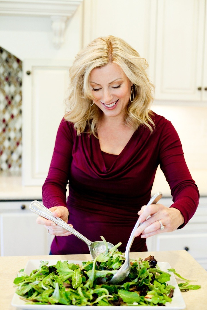 A blond woman in front of a counter using salad tongs to toss Greens with Pomegranate Vinaigrette