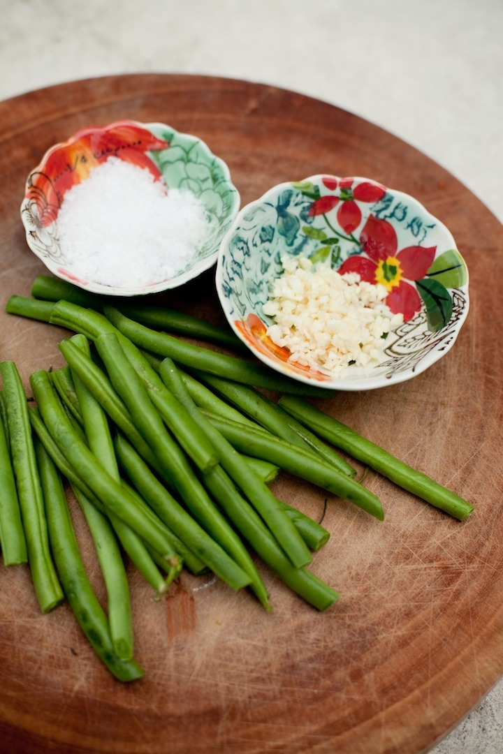 Ingredients for simple blanched green beans: sea salt, garlic and green beans, on a wooden cutting board
