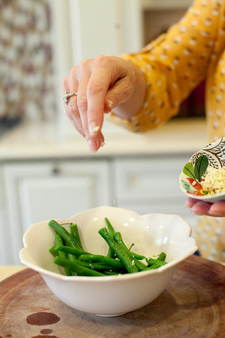 A woman's hand sprinkling minced garlic on a bowl of simple blanched green beans