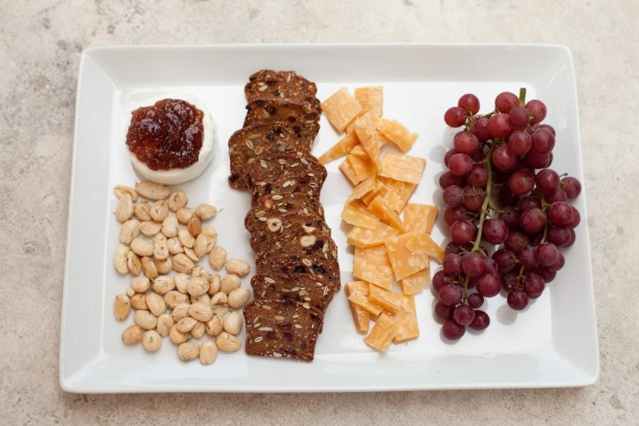 No fuss appetizer platter: A white platter with almonds. crackers, goat cheese, grapes, and gouda cheese, sitting on a marble surface