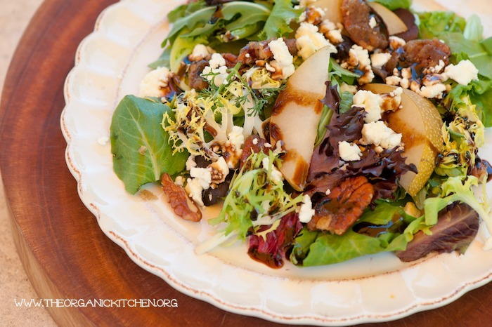 """""""Greens with Asian Pears and Fig/Maple Balsamic Vinaigrette"""" served on a \white plate set on a wooden cutting board"""