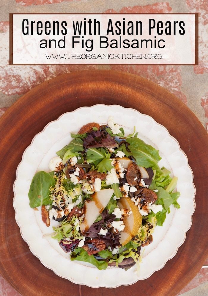 """""""Greens with Asian Pears and Fig/Maple Balsamic Vinaigrette"""" on a white plate with scalloped edges set on a wooden cutting board"""