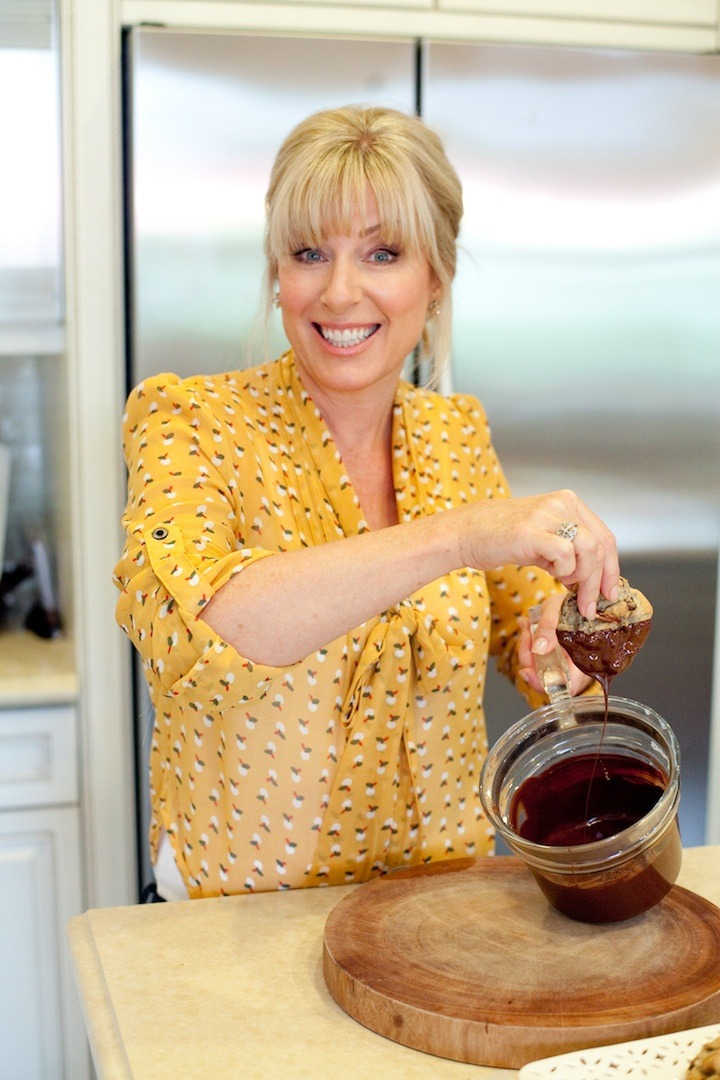 A blond woman with bangs in a yellow blouse dipping a cookie in melted chocolate