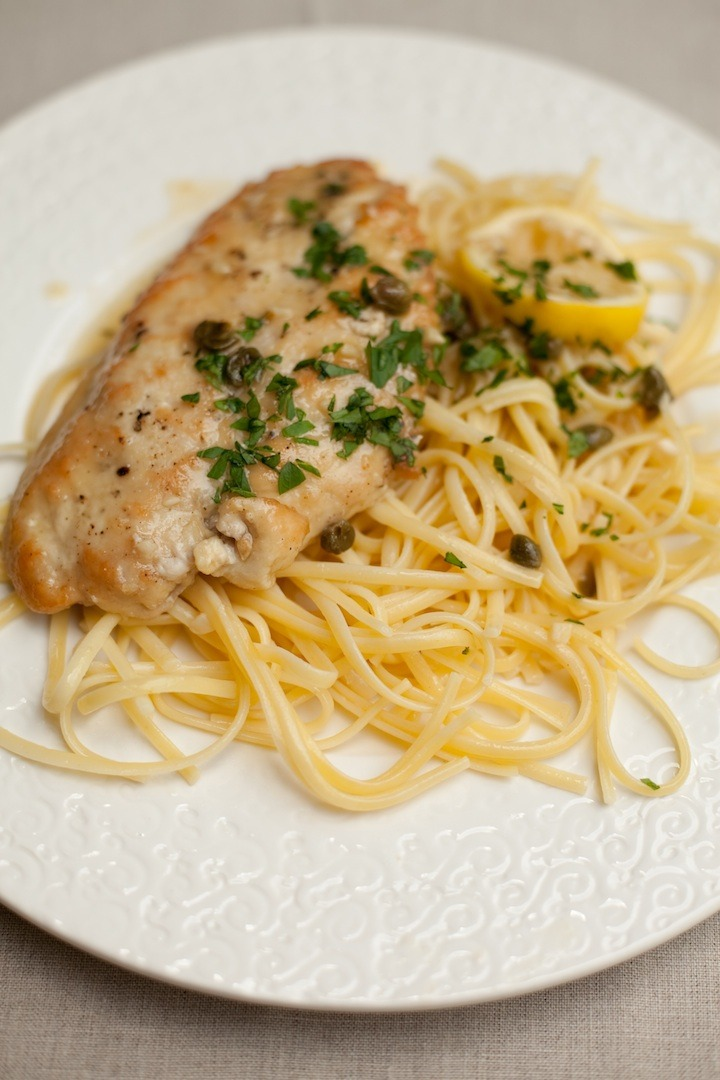 Chicken Piccata on white plate set on a beige table cloth