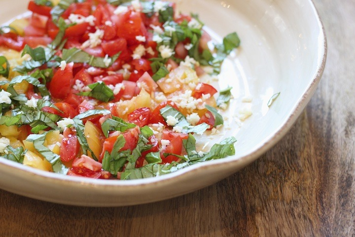 Chopped tomatoes, garlic, and basil in a large white bowl on wooden table. Heirloom Tomato Linguini from The Organic Kitchen