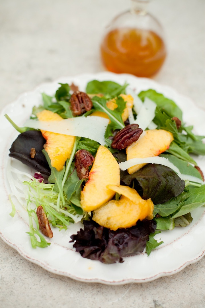 Greens with Peaches set on a white plate with a bottle of vinaigrette