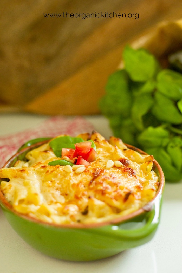 A green baking dish filled with 'baked penne rigate with a kick' on a white surface in front of fresh basil and wood cutting boards