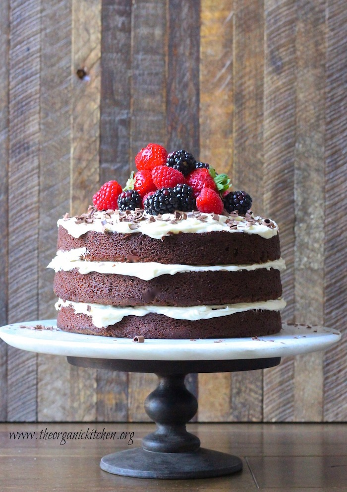 A triple layer Naked Chocolate Cake with Buttercream Frosting topped with colorful berries on cake plate