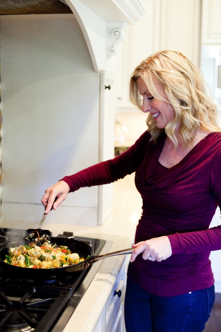 A blond woman at the cooktop grilled vegetables to be used in Grilled Veggie Salad from The Organic Kitchen