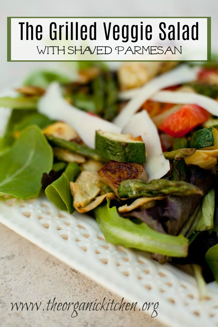 The Grilled Veggie Salad garnished with shaved parmesan, set on a decorative white plate