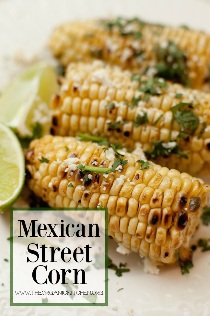 Three cobs of Mexican Street Corn with limes on white surface